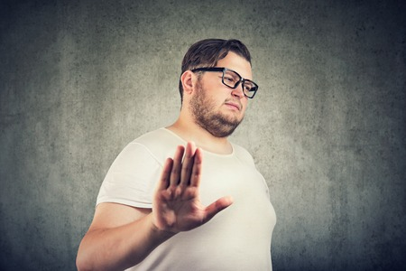Annoyed sad man giving talk to hand gesture isolated on gray background. Negative emotion face expression feeling body language Stok Fotoğraf