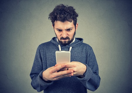 Young bearded man holding smartphone being upset with text message