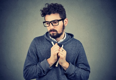 Young bearded man pointing feeling shy and guilty in awkward situation