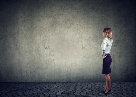 Achteraanzicht van zakenvrouw die bij de muur staat met de hand op het hoofd en zich afvraagt wat ze vervolgens moet doen als ze wordt uitgedaagd. Volledige lengte van zakenvrouw geconfronteerd met het obstakel Stockfoto
