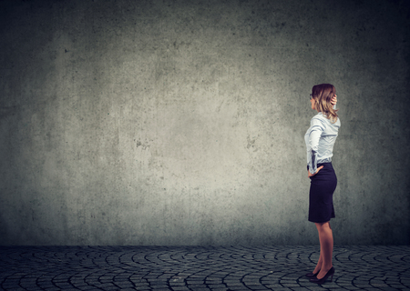 Rear view of business woman standing by the wall with hand on head wondering what to do next being challenged. Full length of businesswoman facing the obstacle Stock fotó