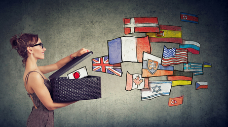 Young woman speaks different languages opening a box with international flags flying away Stock Photo
