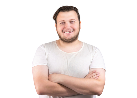 Portrait of young chubby man in white t-shirt holding arms crossed and smiling at camera on white background Reklamní fotografie