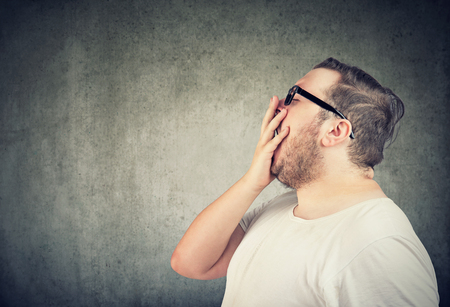 Side view of chubby man in white t-shirt and glasses covering mouth while yawning on gray background