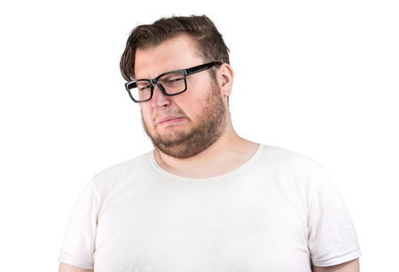 Young bearded man in glasses frowning of bad smell looking deeply displeased on white background