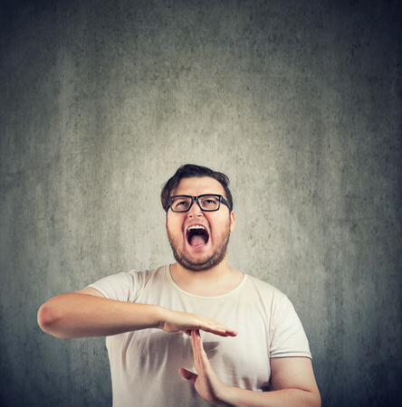 Casual obese man in glasses yelling in annoyance and gesturing for time out on gray background Stock Photo
