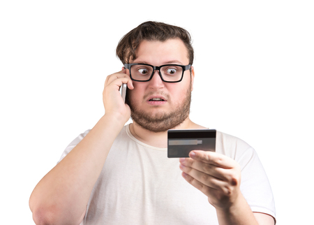 Adult chunky man in glasses holding credit card with stress while speaking on phone
