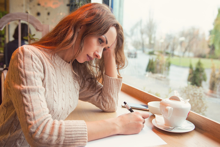 Sad young woman writing letter with broken heart feeling desperate