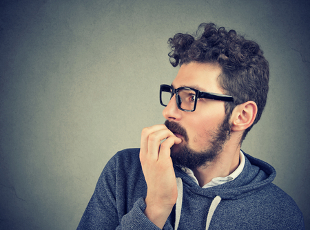 adult man in glasses biting nails being in panic and anxiety looking to the side