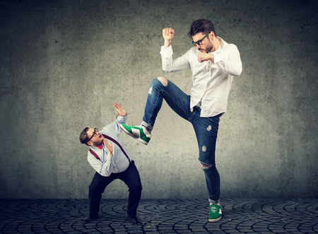 Little business man being crushed by a giant hipster guy Banque d'images - 113699608