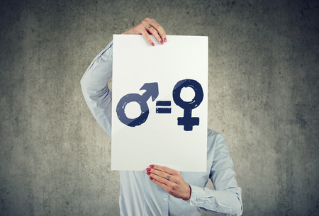 Gender equality concept. Business woman holding a white paper with male and female symbol on gray wall background.