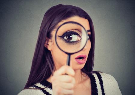 Jeune femme curieuse regardant à travers une loupe Banque d'images