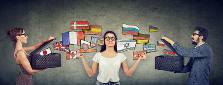 Young girl meditating learning different languages being exposed to different cultures by man and woman with opened boxes and international flags flying away Stock Photo