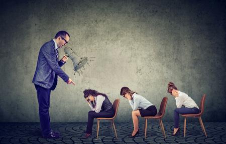 Autoritaire boze baas zakenman die in megafoon schreeuwt en bevelen geeft aan verdrietig neerkijkende vrouwelijke werknemers