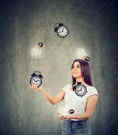 Smart time management concept. Happy young woman juggling bright lightbulbs and alarm clocks