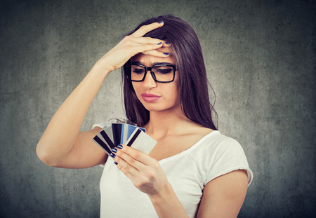 Confused stressed woman looking at too many credit cards full of debt  版權商用圖片