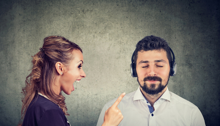 Angry woman yelling at a calm husband listening to music with headphones   Foto de archivo
