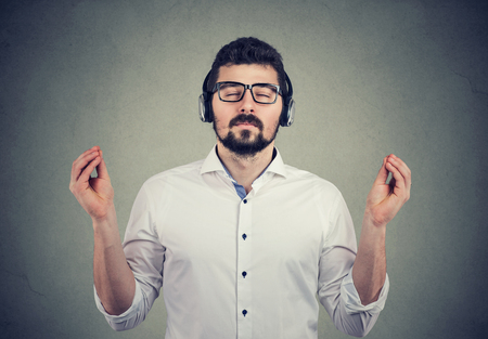 Porträt eines gutaussehenden Mannes mit Kopfhörern mit geschlossenen Augen, der Musik hört und meditiert Standard-Bild