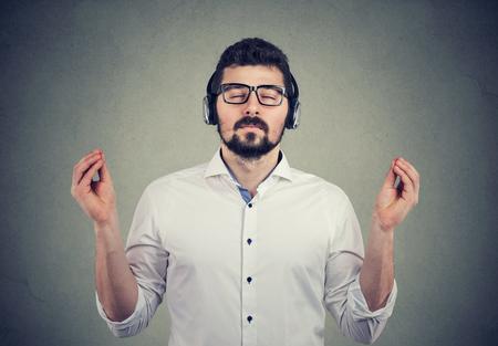 Portret van een knappe man in koptelefoon met gesloten ogen die naar muziek luistert en mediteert Stockfoto