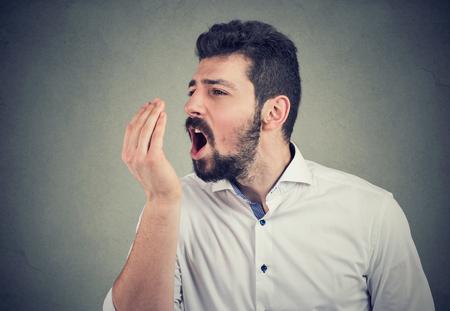 Uomo con la barba che fa un test del respiro alla mano Archivio Fotografico
