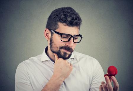 Verwarde jongeman die naar een verlovingsring kijkt en twijfelt Stockfoto