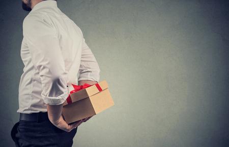 Close-up van een man in een wit overhemd die een geschenkdoos achter zijn rug houdt terwijl hij tegen een grijze muurachtergrond staat Stockfoto