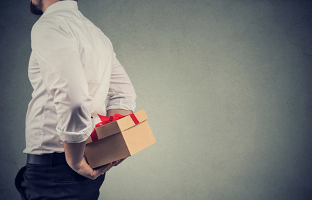 Closeup of a man in white shirt holding a gift box behind his back while standing against gray wall background Banque d'images