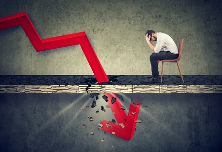 Depressed business man looking down at the falling red arrow going through a concrete floor. Fall and depreciation concept. Stock Photo