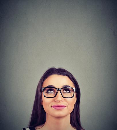 hübsche junge Frau mit Brille, die nach oben schaut