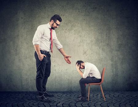 Gran empresario dando una mano apoyando a un pequeño emprendedor desesperado deprimido Foto de archivo