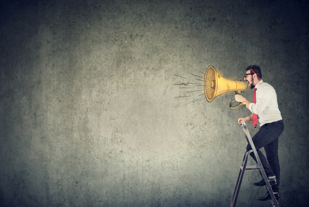 Business man standing on a ladder and screaming into a megaphone Stock Photo