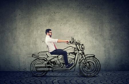 glücklicher Hipster-Geschäftsmann, der ein Motorrad fährt Standard-Bild
