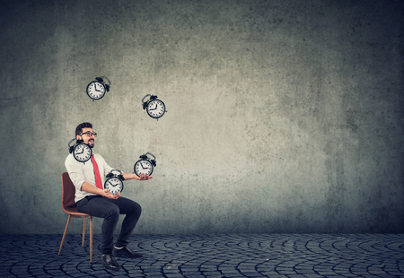 Happy business man successfully juggling alarm clocks managing his time