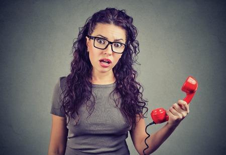 Giovane donna risentita e scioccata che guarda con incredulità tenendo la cornetta del telefono