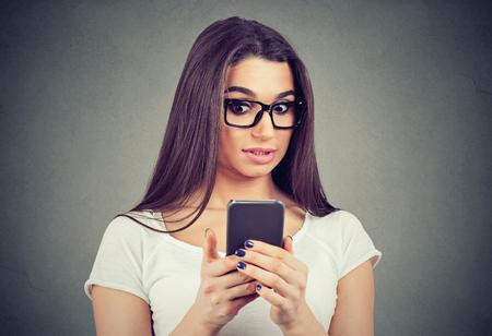 Conmocionada joven mirando su teléfono móvil viendo malas noticias o fotos
