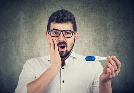 Shocked man holding a positive paternity or pregnancy test feeling anxious