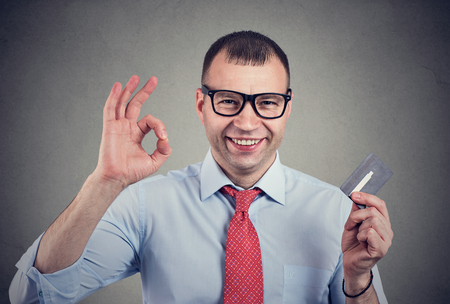 Cheerful happy business man with credit card showing Ok sign on gray background