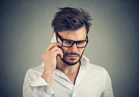 Biznesmen ze smutnym wyrazem twarzy rozmawia przez telefon komórkowy patrząc w dół