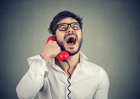 Lustiger Typ am roten Telefon Standard-Bild