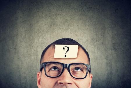denkender Mann in Gläsern mit Fragezeichen, das auf grauem Wandhintergrund nach oben schaut