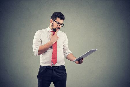 Thoughtful business man touching chin and using tablet computer