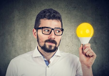 Curious young man holding looking at bright light bulb