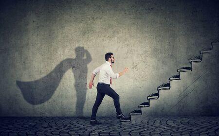 Hombre de negocios de superhéroe subiendo escaleras subiendo hacia el éxito sobre fondo de pared gris