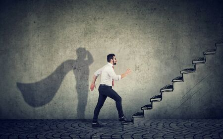 Super hero business man stepping up on stairs climbing to success on gray wall background