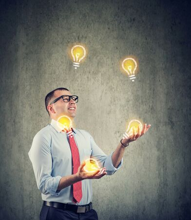 Young businessman juggling with new ideas light bulbs