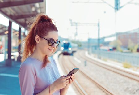Young woman using her cell phone on subway platform, checking message sms e-mail or train schedule. Girl texting on smartphone while city train approaches