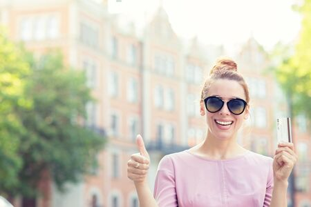 Cheerful excited young woman with credit card giving thumb up standing outdoors on a sunny street with apartment condo on a background