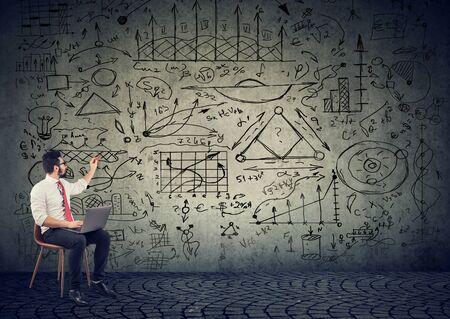 Zakenman met computer die de strategie van het businessplan op de muur trekt Stockfoto