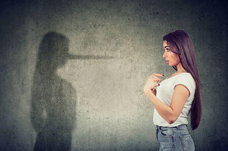 Seitenansicht einer Frau, die auf sich selbst zeigt und einen Schatten mit langer Nase eines Lügners betrachtet.
