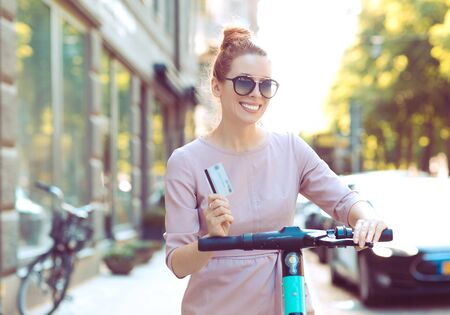 young cool woman with credit card renting an electric scooter ready to explore the city
